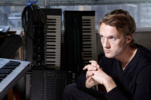 Man sits with crossed hands in front of several keyboards.