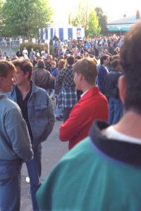 Closeup to extreme longshot of crowd waiting outside hockey arena.