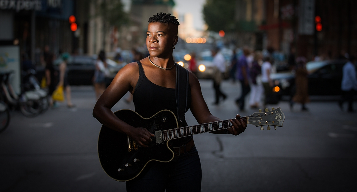 Cecile Doo-Kingue with guitar against the background of the street
