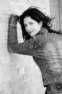 black and white picture woman leaning on brick wall