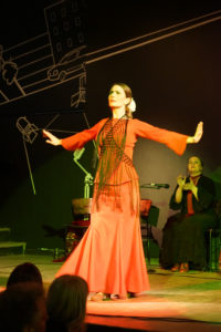 Female dancer  standing,in red, arms raised with palms upward.
