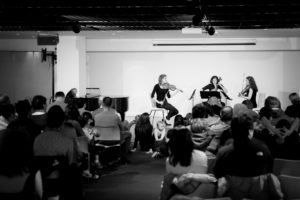 Three female musicians, holding their violin, cello, and viola onstage.