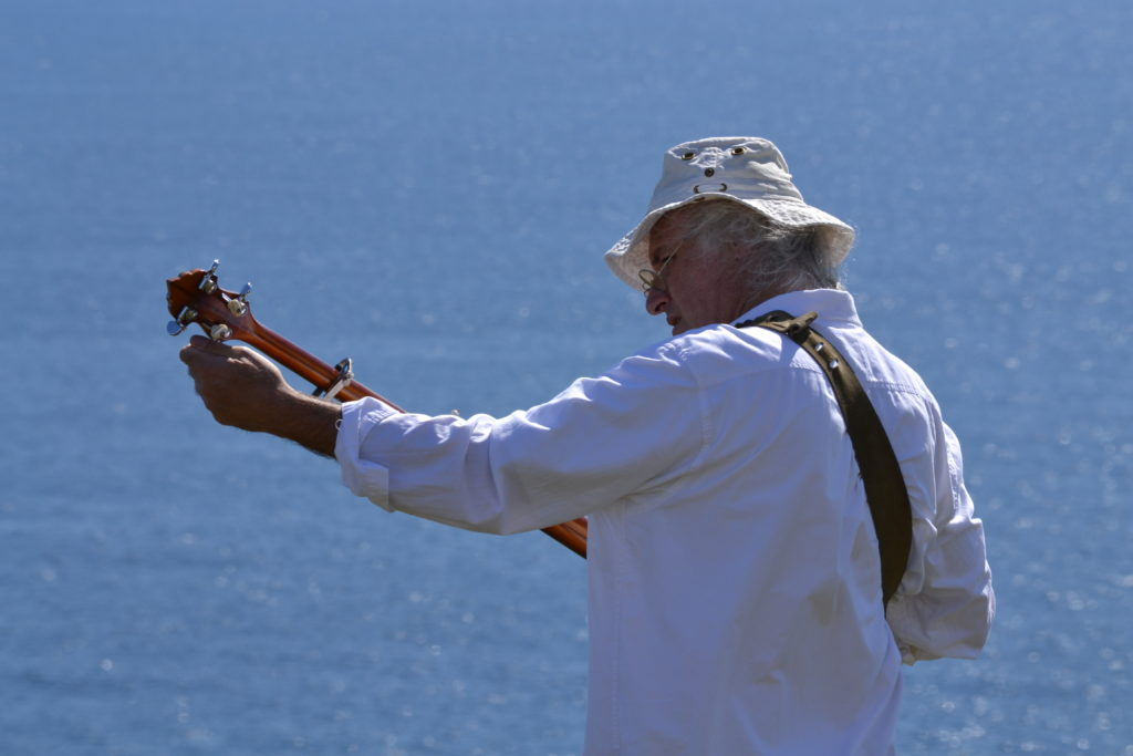 Man tunes his guitar next to a body of water