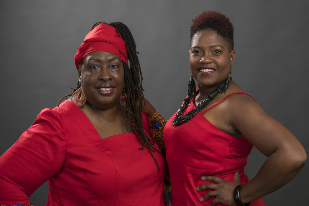 2 women in red smiling at camera