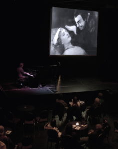 pianist in front of audience, with old film in background
