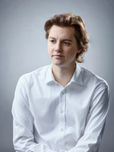 Young man in white shirt looking down to the side.