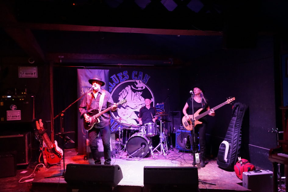 Male guitarist, male drummer and female bassist onstage in club.