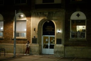 Woman outside an old building at night on her phone