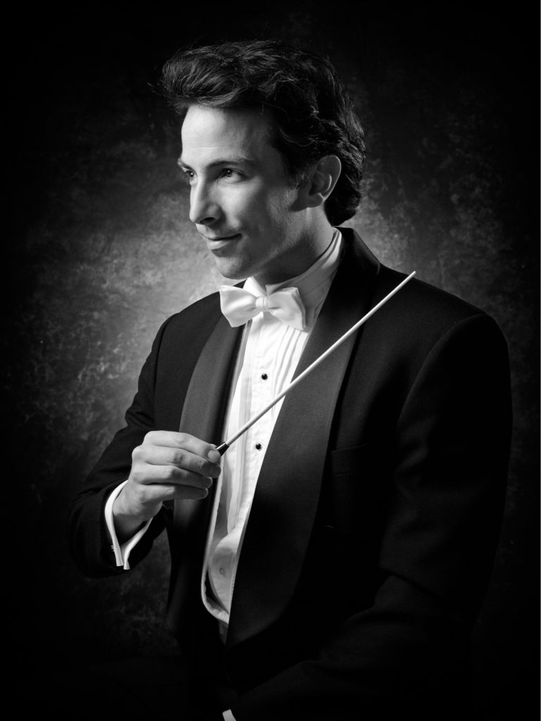 Bust shot of man, bow tie and tuxedo, baton raised