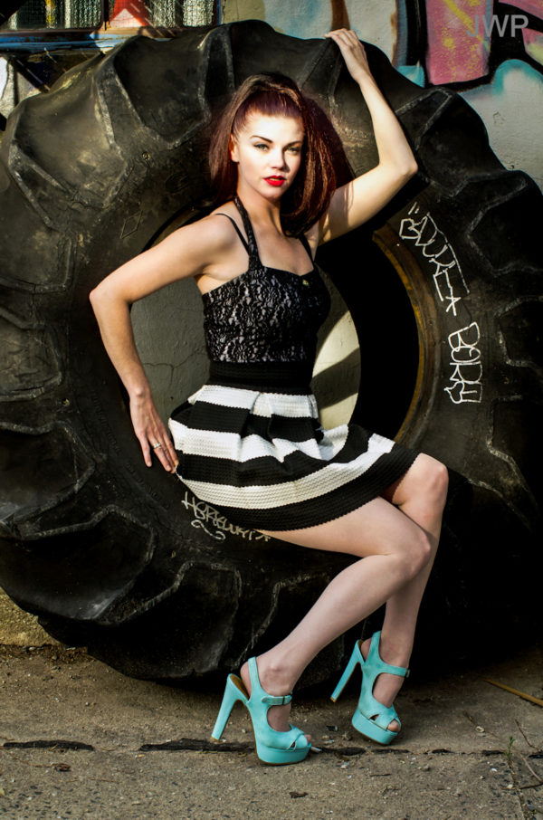 Woman in dress and heels lounging in unmounted giant tire