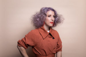 purple-haired woman in orange, arms akimbo, looking into distance