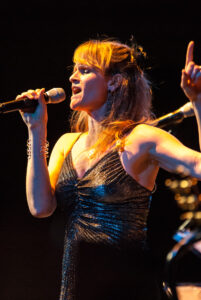 Blonde-haired woman in shiny dark top singing with microphone