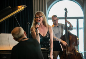 Female vocalist, male pianistand bassist performing live onstage
