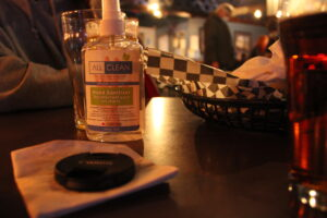 Hand Sanitizer, glass and lens cap on a small table