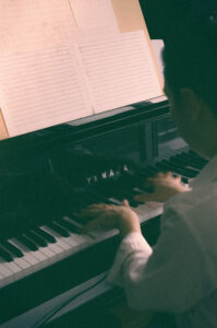 looking over man's shoulder as he plays piano at home