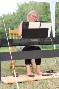 Closeup of woman onstage outdoors seated at electric piano