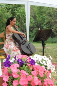 Woman in light dress sits playing electric cello behind flowers